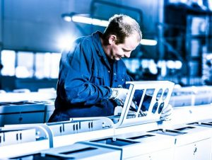 עובד מבצע הרכבה מכאנית של מכלול על גבי פס הרכבה.